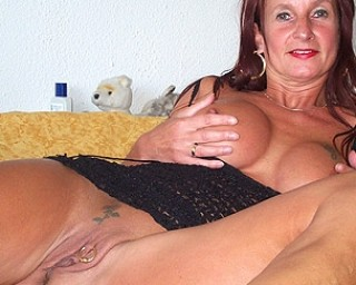 Shaved mom playing on her bed
